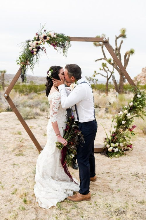 a boho hexagon wedding arch with greenery and grasses, blusha nd burgundy blooms for a boho fall wedding