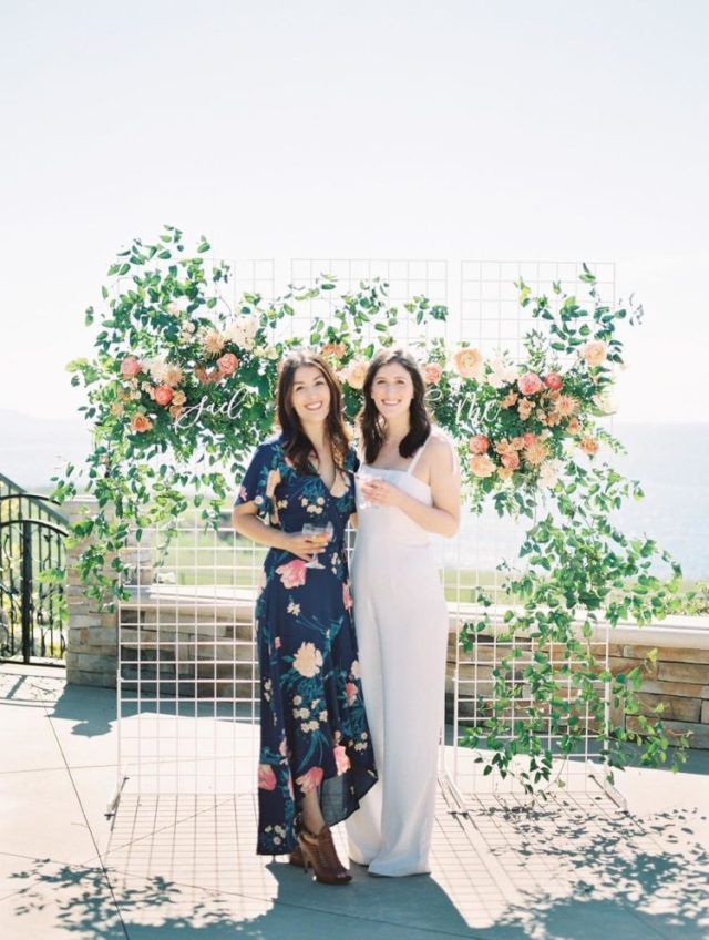 The backdrop was made of a white grid with lush greenery and peachy pink blooms plus calligraphy