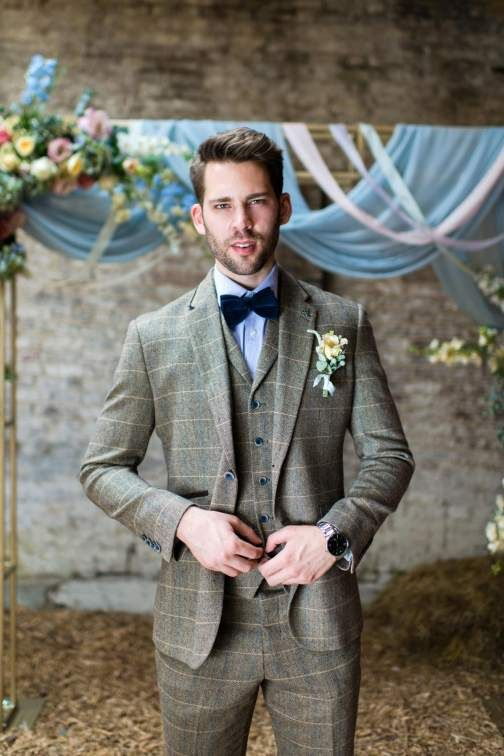 a brown windowpane print three-piece suit with blue buttons, a blue shirt, a navy velvet bow tie