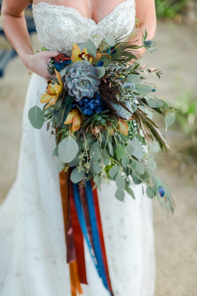 The wedding bouquet was done with lots of greenery, rust and blue flowers, succulents and even peacock feathers