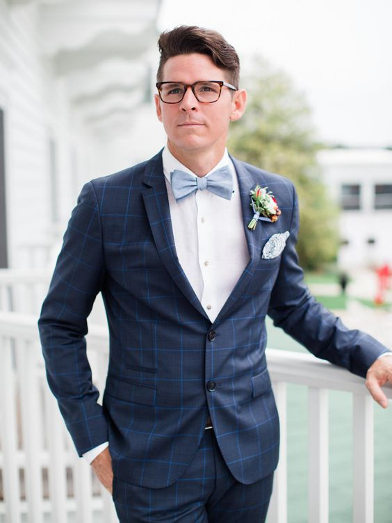 a chic navy windowpane print suit, a white shirt, a powder blue bow tie and a colorful floral boutonniere