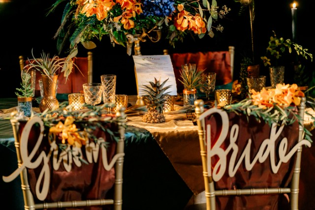 The reception was truly exotic, with lots of candles, gilded touches, lush florals and air plants and pineapples for decor