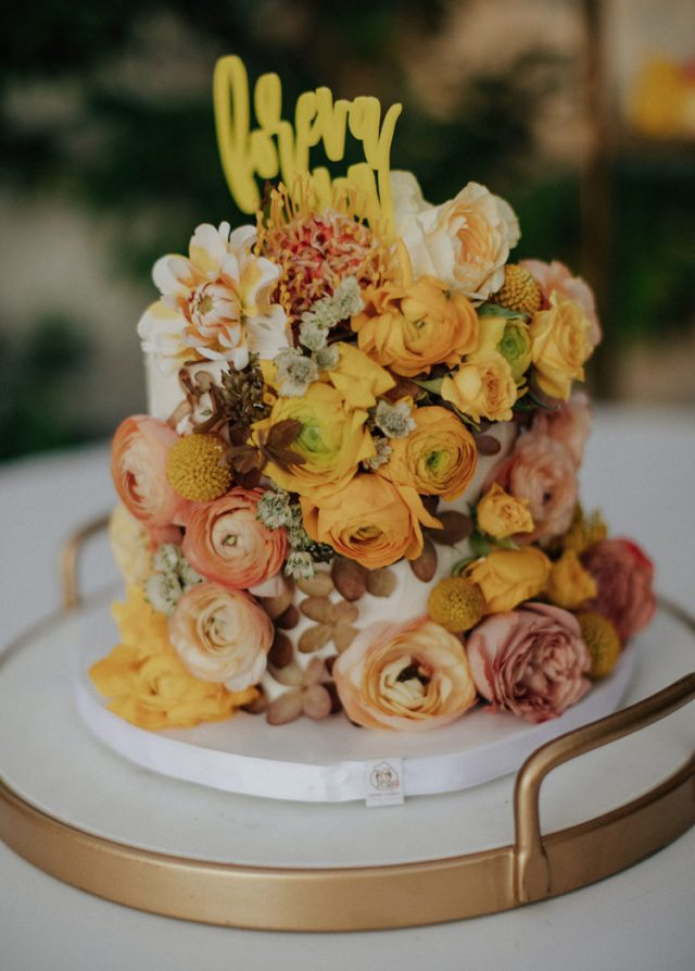 The wedding cake was very whimsy, it was all covered with yellow and rust blooms plus a calligraphy topper