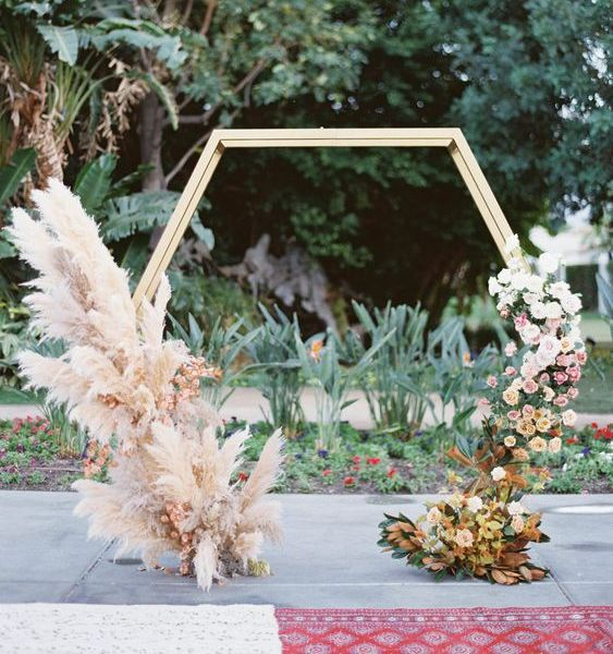 a hexagon wedding arch decorated with pampas grass and pink blooms on one side and ombre blooms on the other side, from whiet to rust