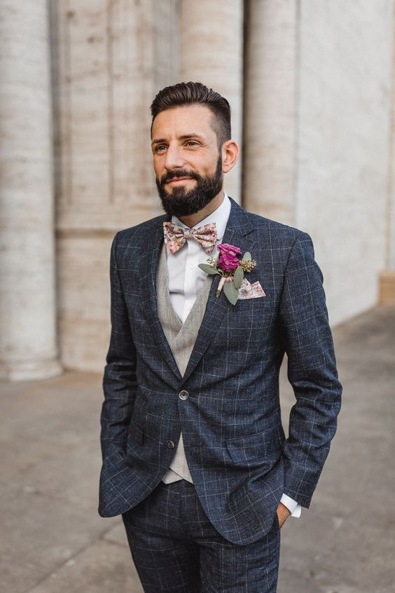 a graphite grey checked suit, a grey waistcoat, a white shirt and a printed floral bow tie plus a matching handkerchief