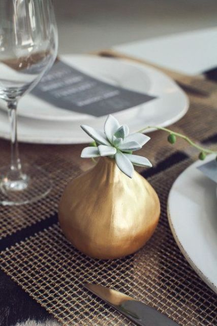 a pear-shaped gilded vase with a single pale succulent is a stylish and simple minimalist wedding centerpiece