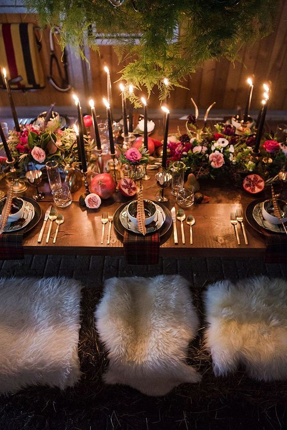 a refined wedding tablescape with ferns hanging over it, black candles, lush moody florals, feathers and pomegranates