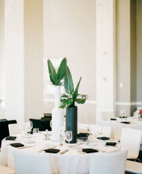 a black and white vase with tropical leaves is a chic and bold idea for a minimalist tropical wedding