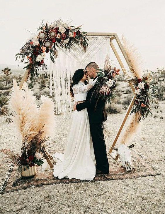 a hexagon wedding arch with a macrame hanging, pampas grass, lush white and pink blooms and foliage for a boho wedding