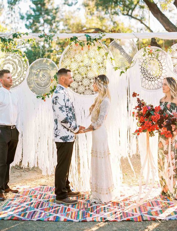 a wedding backdrop of oversized macrame dreamcatchers plus greenery and bright blooms for a boho wedding
