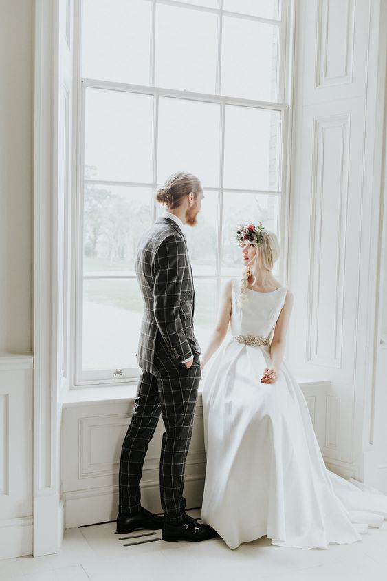 a grey windowpane print suit, a white shirt, black shoes and black socks for a bold modern groom's look