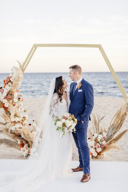 a luxurious hexagon wedding arch decorated with blusha nd dusty pink blooms, white flowers and pampas grass for an oceanfrotn ceremony