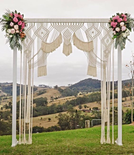 a bright macrame wedding arch with pink and blush blooms and greenery on the corners