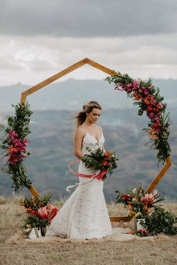 a bright polygon wedding arch decorated with pink blooms and lush greenery for a summer wedding