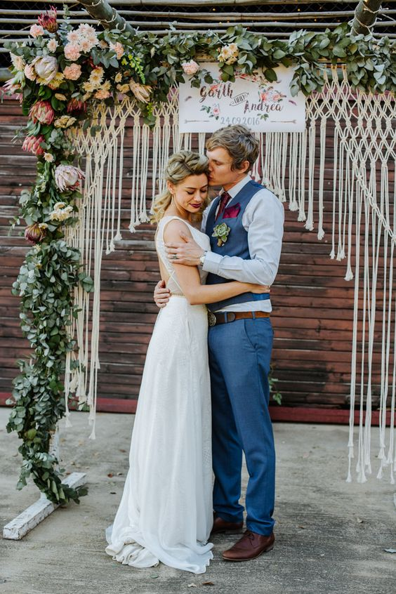 a bright summer wedding arch with macrame, lush greenery, pink, blush and fuchsia blooms