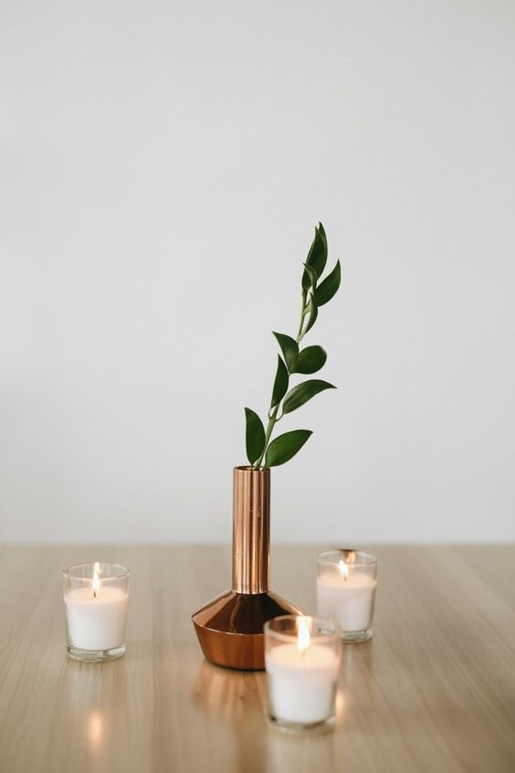 a minimalist wedding centerpiece of a copper vase and a single greenery branch plus candles all around