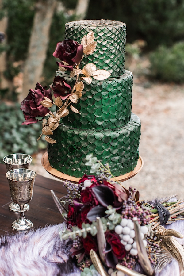 a fantastic green dragon scale wedding cake with sugar red roses and gilded greenery is a very elegant idea