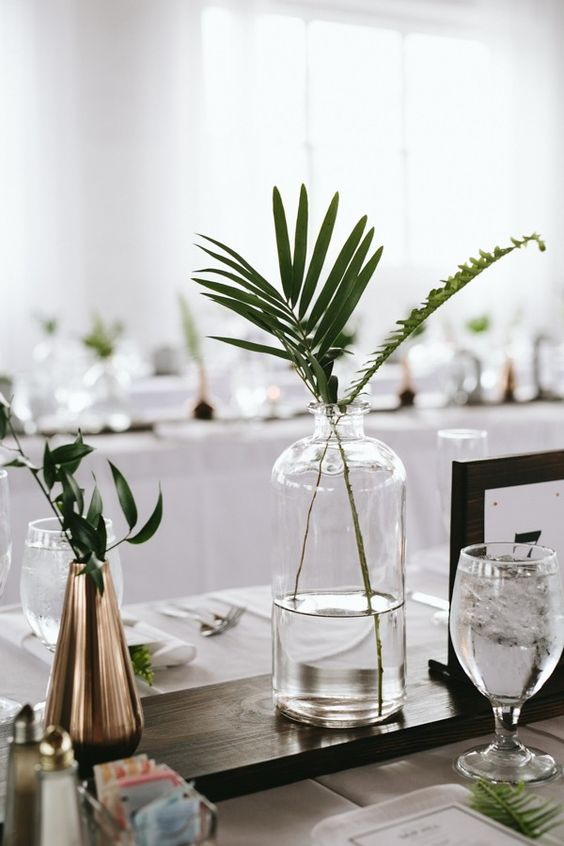 a minimalist wedding centerpiece with greenery in a clear and metallic vase on a dark stained board