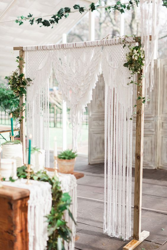 a simple and chic macrame wedding arch with some greenery on each corner is a cool idea