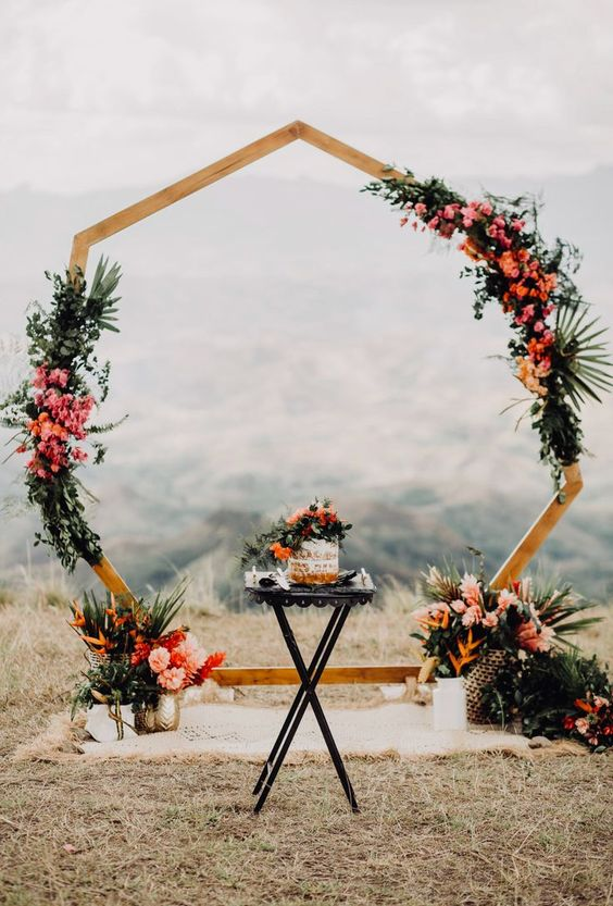 a polygon wedding arch decorated with greenery and tropical leaves, bright orange and pink blooms and tropical fruits