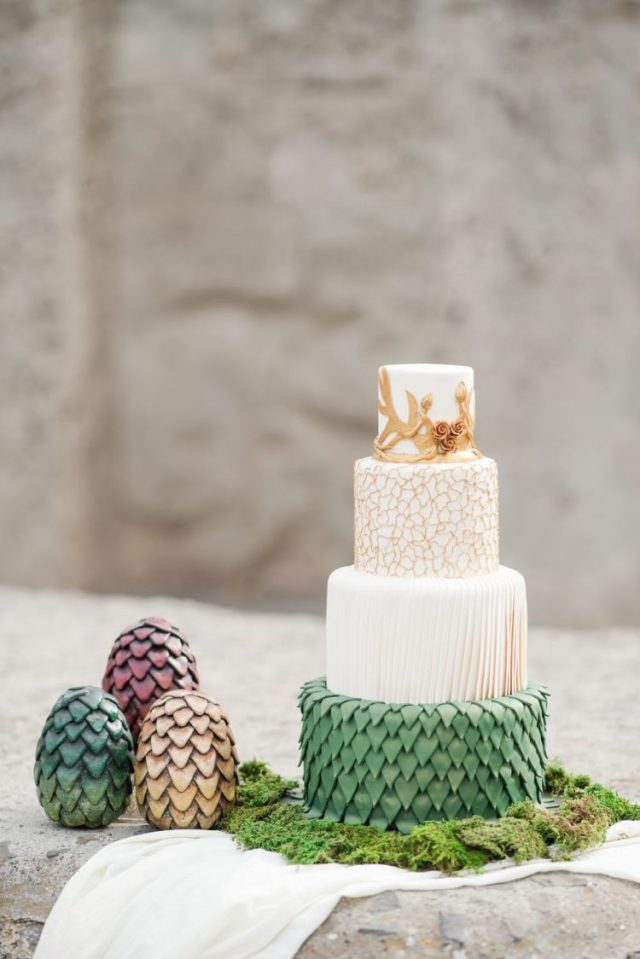 a GOTH wedding cake with a draped, green scale, gold crack and antlers all done with sugar scream