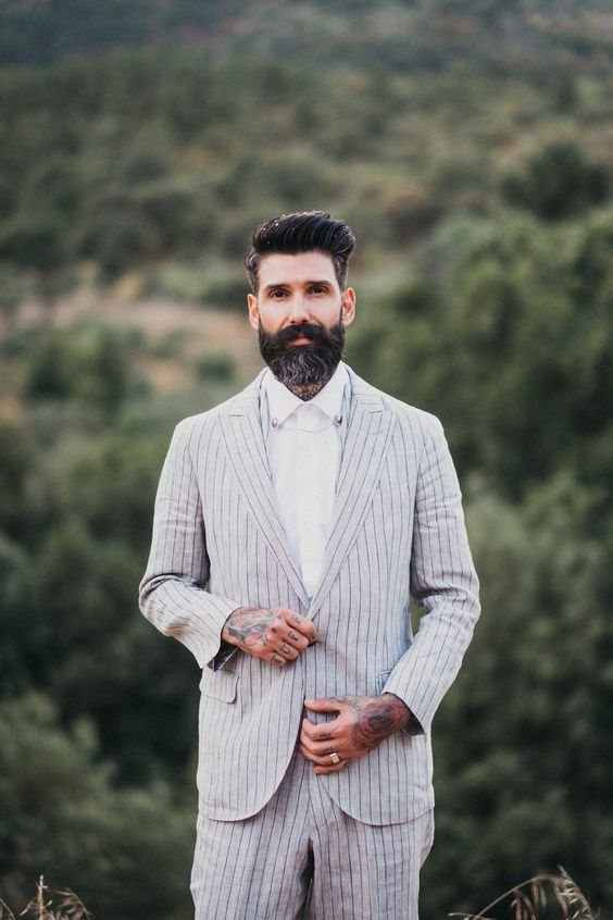 a relaxed boho groom look with a neutral striped linen suit and a white shirt for a hot day