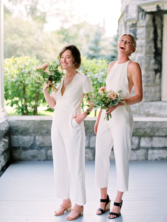 mismatching white bridesmaid jumpsuits with pockets and various shoes for a modern wedding
