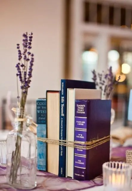 a bundled books centerpiece and some candles plus lavender in bottles around make up simple and stylish decor