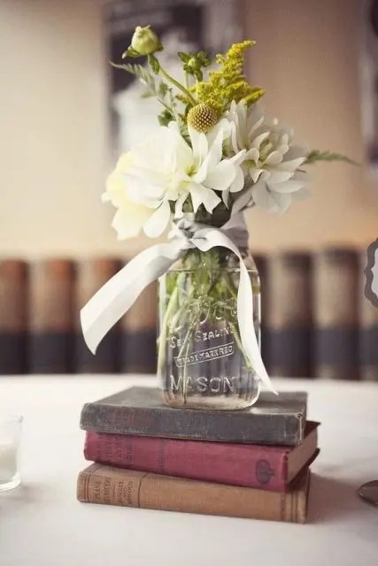 a stack of vintage books with a floral arrangement in a jar is a chic idea to try