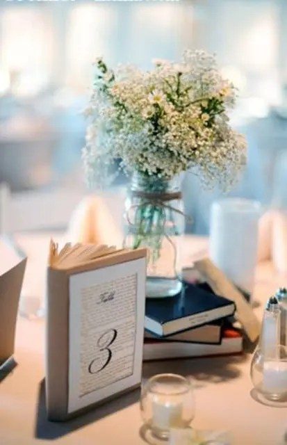 some books and a white floral arrangement in a jar is a proper idea to decorate a rustic wedding