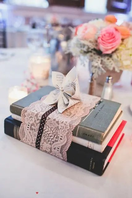 a vintage book wedding centerpiece - s stack wrapped with lace and with a paper bloom