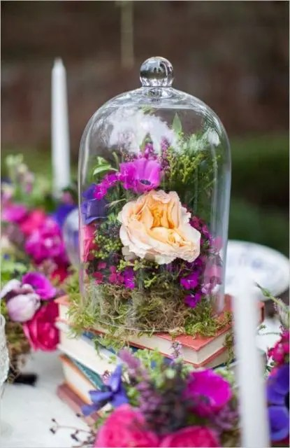 a stack of books with a cloche filled with moss and bright blooms is a gorgeous idea of wedding decor