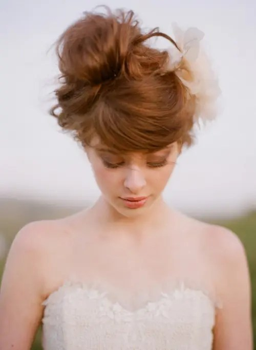 a messy wavy updo with bangs and a large faux flower for a modern bride with a touch of romance