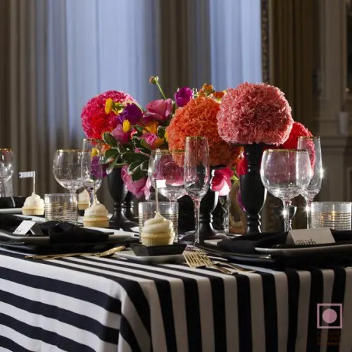 a black and white striped tablecloth, black candle holders with red blooms