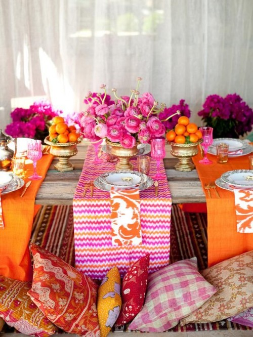 a colorful boho tablescape with bright pink and orange textiles, bright blooms and citrus and gold touches