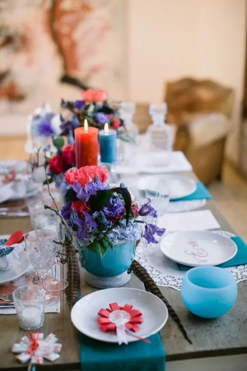 a super bright boho tablescape in turquoise and red, with candles, blooms, bright textiles
