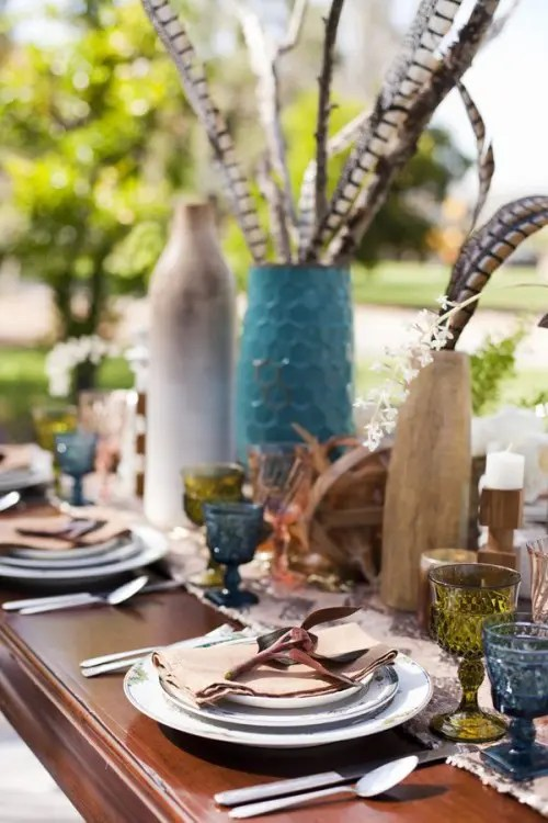 vases with feathers, colored glasses, candles and printed plates for a simple boho tablescape