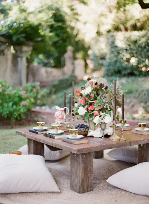 a low picnic table with candles, a lush floral centerpiece, books instead of placemats and vintage teacups