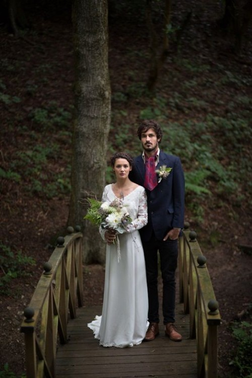 a navy suit, a white button down. a plum-colored vintage tie, brown shoes and a greenery boutonniere for a winter woodland wedding