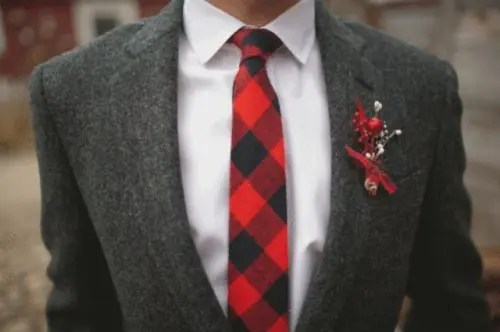 a grey tweed suit, a white button down, a red checked tie and a red boutonniere to add color to the look