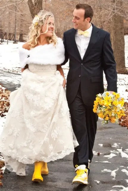 a black suit, a white button down, a yellow bow tie and matching boots for a bright and fun winter groom's look