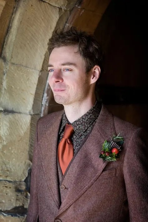 a burgundy tweed three-piece suit, a moody floral shirt, a rust tie and a berry boutonniere