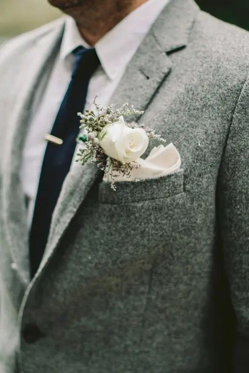 a grey tweed suit with a white button down, a navy tie and a white floral boutonniere