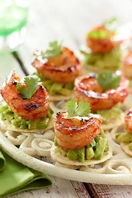 crackers with avocado drip, grilled shrimps and herbs on top is a refined idea