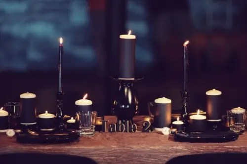 a modern gothic wedding tablescape with black candles, black plates and an uncovered table