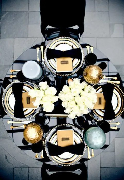 a chic wedding tablescape with a white rose centerpiece, large candles and ornaments and gold cutlery