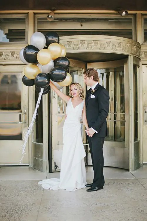 the groom wearing black, the bride wearing white and gold and black balloons