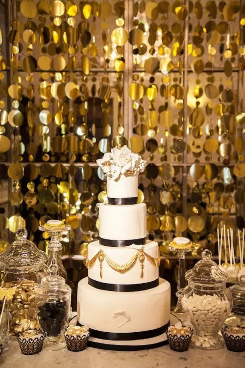 a black and white wedding cake, a black, white and gold wedding dessert table and a gold backdrop