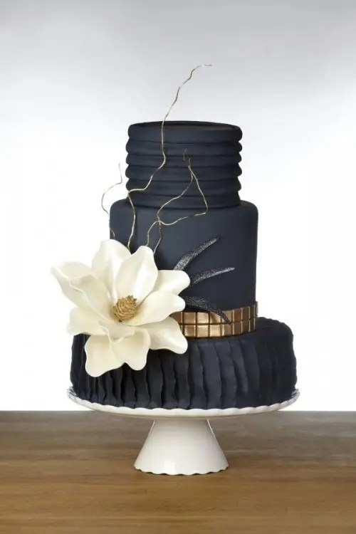 a textural black and gold wedding cake topped with a white sugar bloom