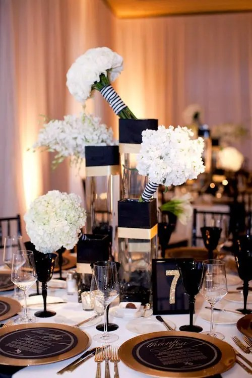 black and white floral centerpieces, a black and gold table number, black glasses and gold chargers